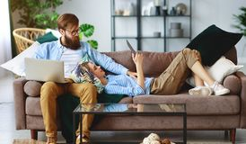 Happy couple relaxing at home with laptop and tablet royalty free stock photo