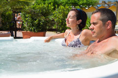Happy couple relaxing in hot tub. Vacation. Royalty Free Stock Images