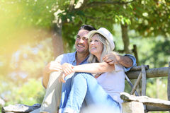 Happy couple relaxing outdoors on the bench Stock Images