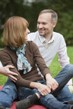 Happy couple relaxing in park stock photography