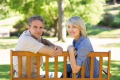 Happy couple relaxing on park bench Stock Image