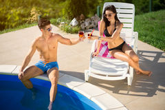 Happy couple relaxing by pool Stock Image