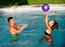 Happy couple relaxing in the pool playing with a ball Stock Photos