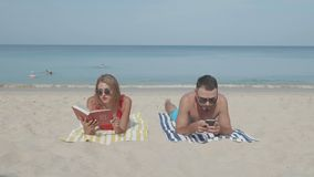 Happy couple relaxing on the beach. Happy couple relaxing on the sandy tropical beach during sunny summer day stock footage