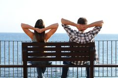 Happy couple relaxing sitting on a bench on the beach. Back view of a happy couple relaxing sitting on a bench contemplating ocean on the beach stock photos