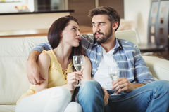 Happy couple relaxing on sofa and holding glasses of champagne Stock Photography