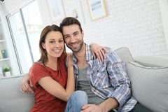 Happy couple relaxing on sofa at home Royalty Free Stock Photography