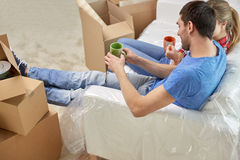 Happy couple relaxing on sofa in new home Stock Images