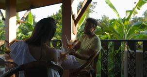 Happy Couple Relaxing On Summer Terrace At Sunset Talking, Young Man And Woman Having Rest Communicating Together. Drinking Juice Slow Motion 60 stock video footage