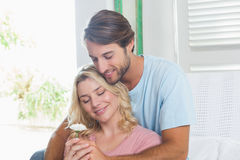 Happy couple relaxing together on the couch with girl holding flower Stock Images