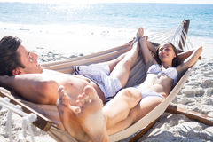 Happy couple relaxing together in the hammock and smiling at each other Stock Photo