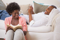 Happy couple relaxing together reading book and using smartphone Royalty Free Stock Photos