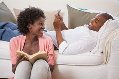 Happy couple relaxing together reading book and using smartphone Stock Photo