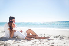Happy couple relaxing together in the sand Royalty Free Stock Image