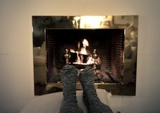 Happy couple relaxing under blanket by the fireplace warming up feet in woolen socks. Close up image of couple sitting under the blanket by cozy fireplace stock photos