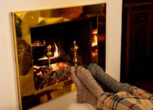 Happy couple relaxing under blanket by the fireplace warming up feet in woolen socks. Close up image of couple sitting under the blanket by cozy fireplace royalty free stock photo