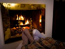 Happy couple relaxing under blanket by the fireplace warming up feet in woolen socks. Close up image of couple sitting under the blanket by cozy fireplace stock photography