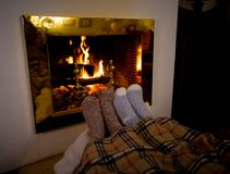 Happy couple relaxing under blanket by the fireplace warming up feet in woolen socks. Close up image of couple sitting under the blanket by cozy fireplace royalty free stock photos