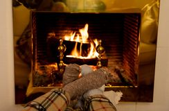 Happy couple relaxing under blanket by the fireplace warming up feet in woolen socks. Close up image of couple sitting under the blanket by cozy fireplace royalty free stock image