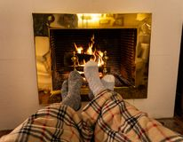 Happy couple relaxing under blanket by the fireplace warming up feet in woolen socks. Close up image of couple sitting under the blanket by cozy fireplace royalty free stock photography