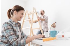 Happy couple remodeling their house. Young smiling couple renovating and remodeling their new apartment, the men is painting the walls with a roller and the Stock Photo