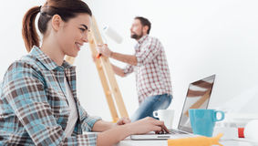 Happy couple remodeling their house. Young smiling couple renovating and remodeling their new apartment, the men is painting the walls with a roller and the Stock Images
