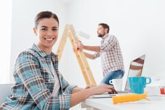 Happy couple remodeling their house. Young smiling couple renovating and remodeling their new apartment, the men is painting the walls with a roller and the Royalty Free Stock Photo