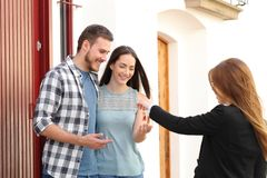 Happy couple of renters receiving house keys. From real estate agent royalty free stock photo