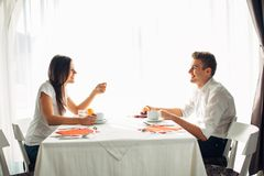 Happy couple at restaurant eating lunch.Talking over meal.Hotel full board,all inclusive stay.Travel, date,food,lifestyle. Smiling people having healthy Stock Image