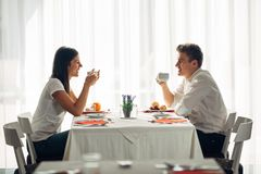 Happy couple at restaurant eating lunch.Talking over meal.Hotel full board,all inclusive stay.Travel, date,food,lifestyle. Smiling people having healthy Royalty Free Stock Photography