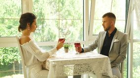 Happy couple in restaurant looking each other and toasting. Cheerful couple in a restaurant with glasses of red wine stock video