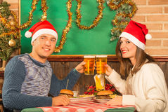 Happy Couple at restaurant with Santa hats royalty free stock photography