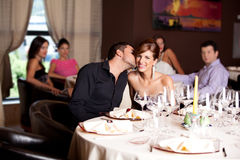 Happy couple at restaurant table kissing Royalty Free Stock Image
