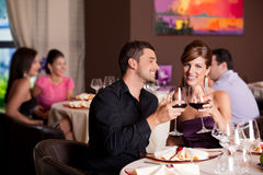 Happy couple at restaurant table toasting. Romantic young couple at restaurant table toasting Royalty Free Stock Images