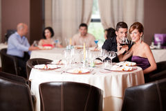 Happy couple at restaurant table toasting Royalty Free Stock Photo