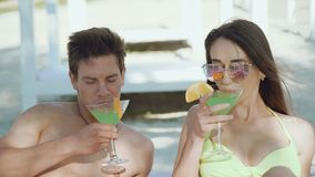 Happy couple resting on the beach, speaking and drinking cocktails 4K. Happy couple resting on the beach, speaking and drinking a cocktails 4K stock footage