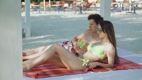 Happy couple resting on the beach, speaking and drinking cocktails 4K. Happy couple resting on the beach, speaking and drinking a cocktails 4K stock video footage