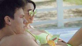 Happy couple resting on the beach, speaking and drinking cocktails 4K.  stock footage