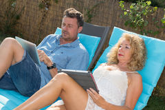 Happy couple resting in deck chairs by pool with tablet Stock Photography