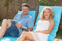 Happy couple resting in deck chairs by pool with tablet Stock Image