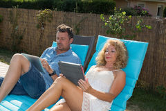 Happy couple resting in deck chairs by pool with tablet Stock Images