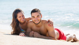 Happy couple resting on sandy beach Royalty Free Stock Photos