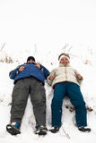 Happy couple resting on snow Stock Images