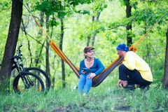Happy couple rests after riding a bikes in the forest. On a awesome sunny day, relaxing in a hammock - wonderful weekend in nature Stock Image