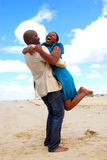 Happy couple reunion. An African American young woman jumping into the arms of her black spouse for a couple reunion on the beach Stock Image