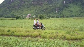 Happy couple rides scooter among fields aerial side view stock video footage