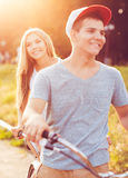 Happy couple riding a bicycle in the city street Stock Photos