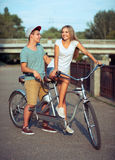 Happy couple riding a bicycle in the city street Stock Image
