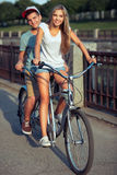 Happy couple riding a bicycle in the city street Stock Images