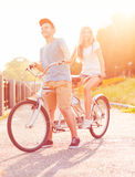 Happy couple riding a bicycle in the city street Stock Photography